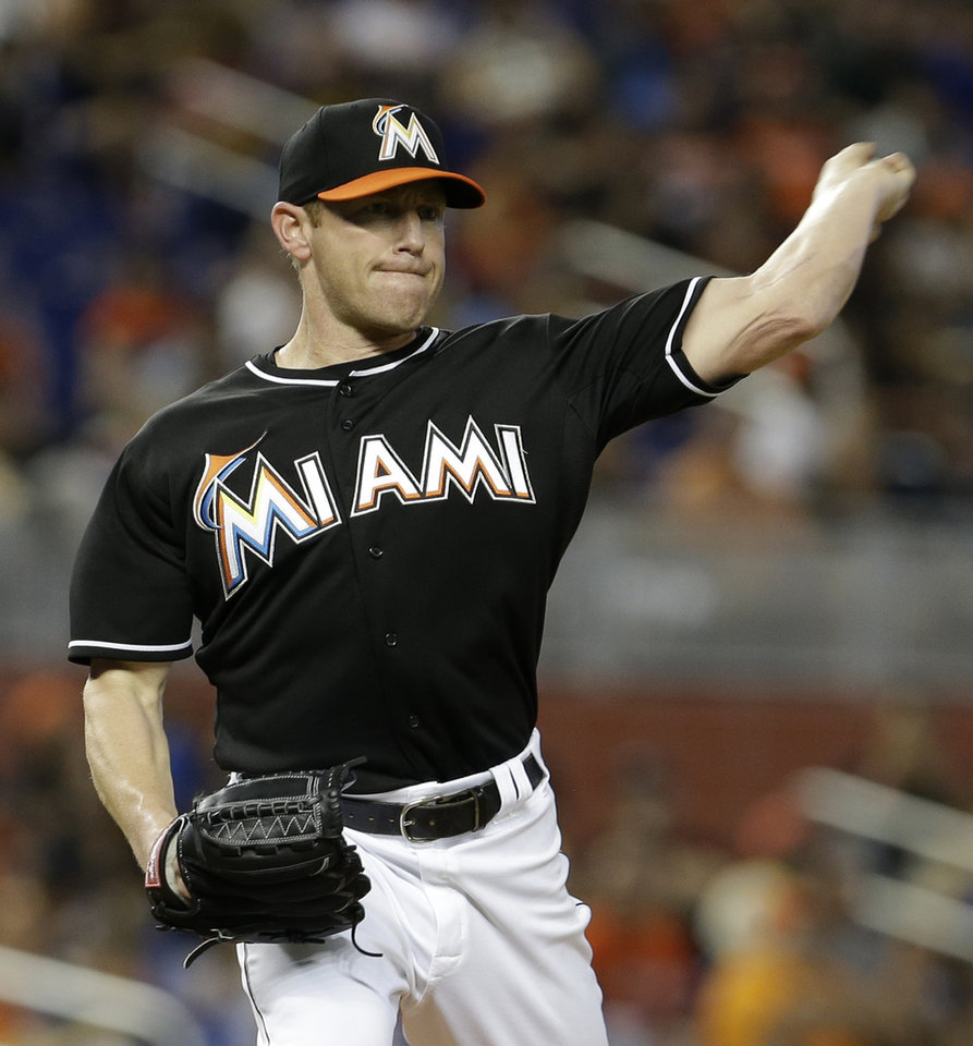 Photo - Miami Marlins' Randy Wolf prepares to throw to first base as he tries to pick off Pittsburgh Pirates' Starling Marte in the first inning of a baseball game in Miami, Saturday, June 14, 2014. (AP Photo/Alan Diaz)
