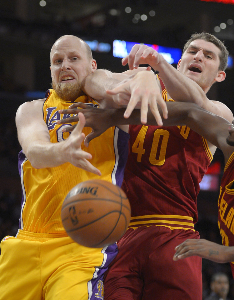 Photo - Los Angeles Lakers center Chris Kaman, left, and Cleveland Cavaliers center Tyler Zeller vie for a rebound during the first half of an NBA basketball game, Tuesday, Jan. 14, 2014, in Los Angeles. (AP Photo/Mark J. Terrill)