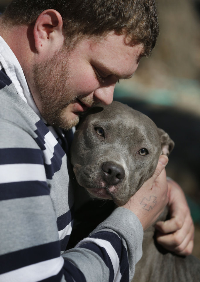 Photo - Cameron Younglove plays with a pit bull terrier named Sooke at his kennels near Eudora, Kan., Sunday, March 9, 2014. The kennel raises their dogs indoors in a family environment and are socialized with other animals to ensure good temperament. (AP Photo/Orlin Wagner)