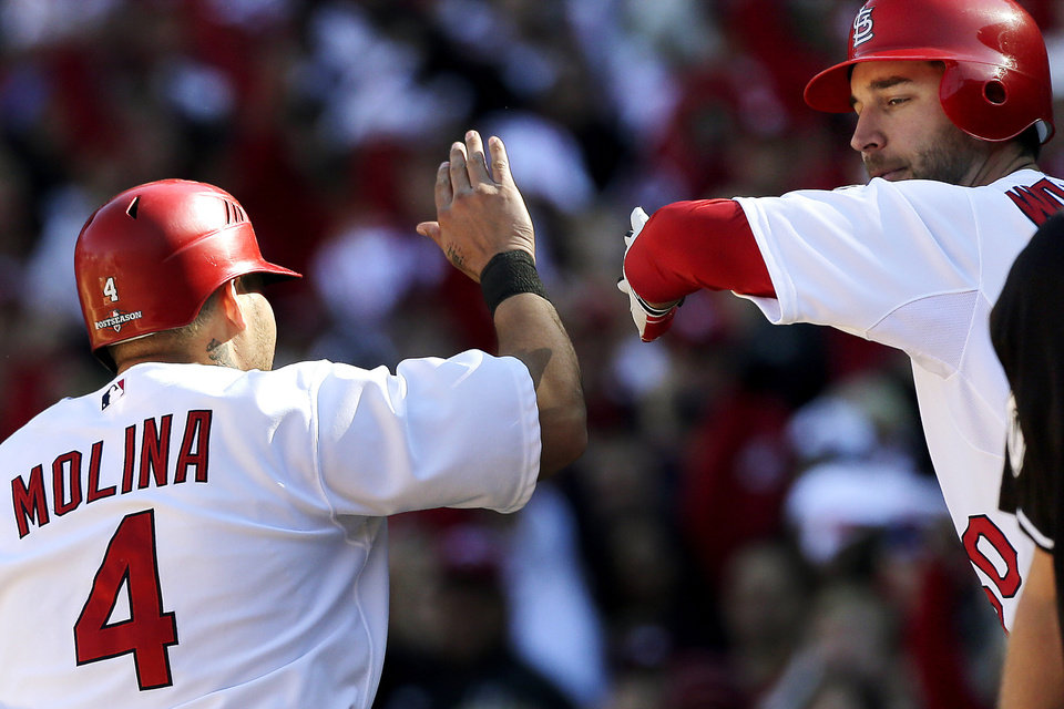 St. Louis Cardinals' Yadier Molina (4) celebrates with Adam Wainwright after Molina scored on a wild pitch during the second inning of Game 1 of the National League division baseball series against the Washington Nationals, Sunday, Oct. 7, 2012, in St. Louis. (AP Photo/Charlie Riedel)