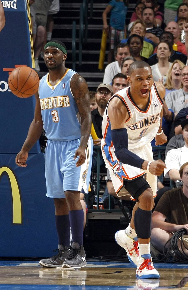 Photo - Oklahoma City's Russell Westbrook (0) celebrates a basket in front of Denver's Ty Lawson (3) during the NBA basketball game between the Oklahoma City Thunder and the Denver Nuggets, Friday, April 8, 2011, at the Oklahoma City Arena.. Photo by Sarah Phipps, The Oklahoman
