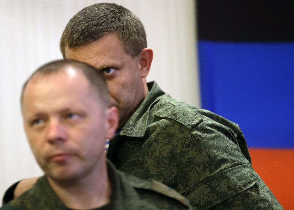 Photo - Prime Minister of the self-proclaimed Donetsk People's Republic Alexander Zakharchenko, right, and Defence Minister Vladimir Kononov leave a news conference in Donetsk, eastern Ukraine, Sunday, Aug. 24, 2014. Ukraine has retaken control of much of its eastern territory bordering Russia in the last few weeks, but fierce fighting for the rebel-held cities of Donetsk and Luhansk persists. (AP Photo/Sergei Grits)