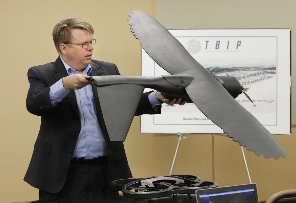 Photo -  James Grimsley, president and CEO of Design Intelligence Incorporated, holds up a MK4 model drone used in wind tunnel tests while talking about drone research and development in Oklahoma during a meeting at the Tinker Business and Industrial Park Monday, April 28, 2014. Photo by Paul B. Southerland, The Oklahoman   PAUL B. SOUTHERLAND -  PAUL B. SOUTHERLAND