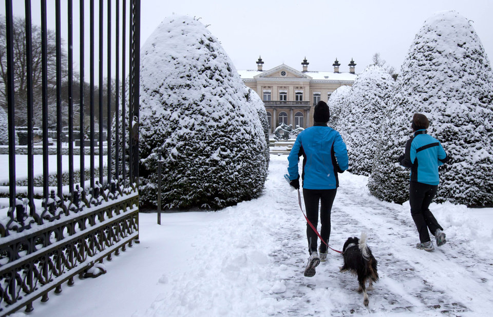 Two runners with their dog make their way down a path covered by snow at a public park in Wilrijk, Belgium on Tuesday, Jan. 15, 2013. Belgium experienced the first snow of the season on Tuesday which snarled traffic in early morning rush hour. (AP Photo/Virginia Mayo)