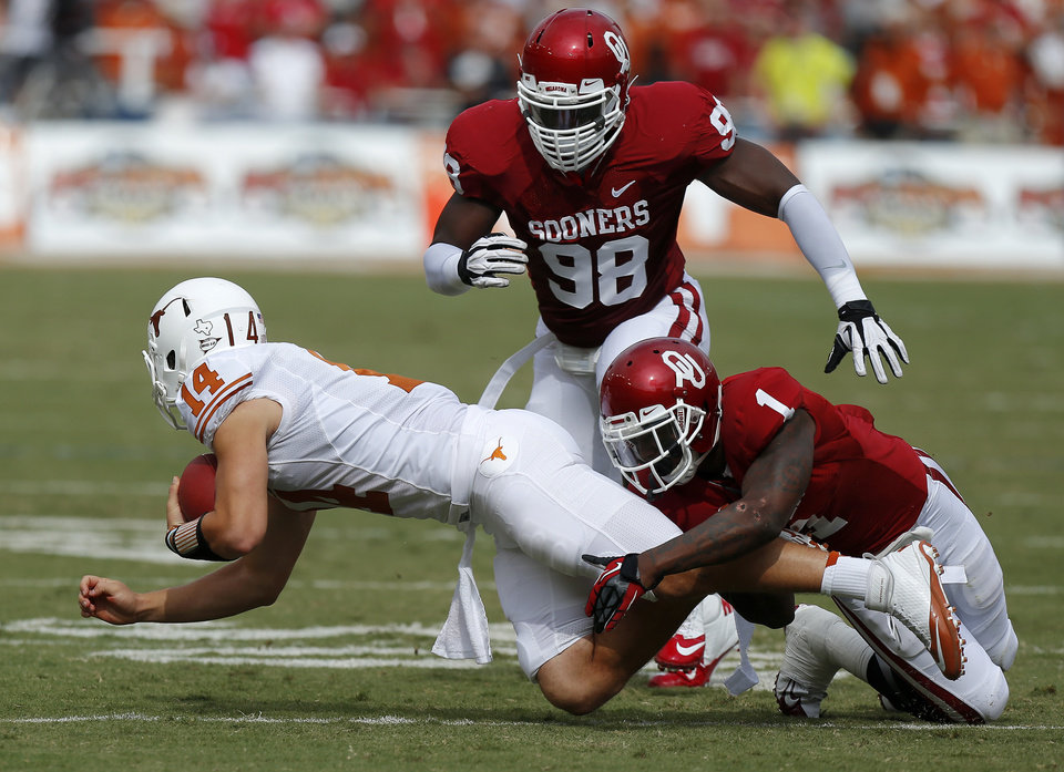 Photo - OU's Tony Jefferson (1) and Tony Jefferson (1) bring down UT's David Ash (14) during the Red River Rivalry college football game between the University of Oklahoma (OU) and the University of Texas (UT) at the Cotton Bowl in Dallas, Saturday, Oct. 13, 2012. Photo by Bryan Terry, The Oklahoman