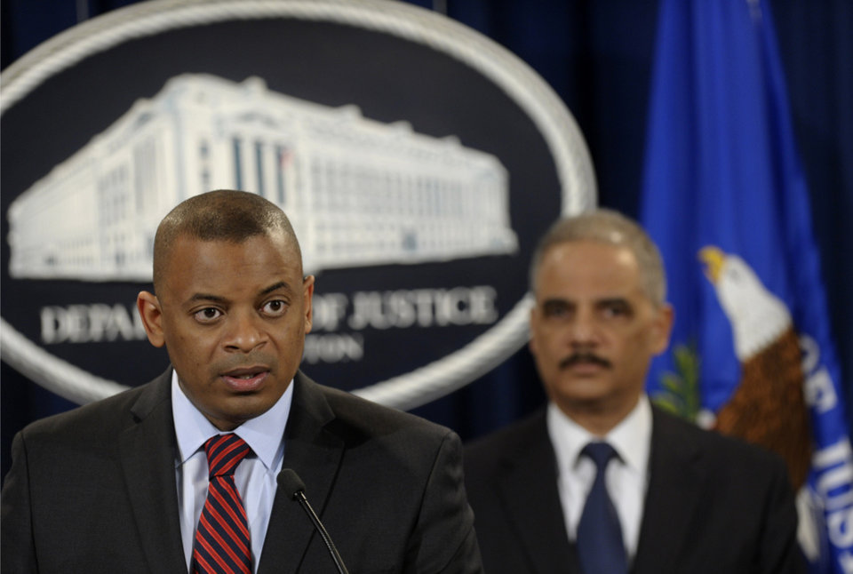 Photo - Transportation Secretary Anthony Foxx. left, accompanied by Attorney General Eric Holder, talks about a $1.2 billion settlement with Toyota over its disclosure of safety problems, Wednesday, March 19, 2014, during a news conference at the Justice Department in Washington.  (AP Photo/Susan Walsh)