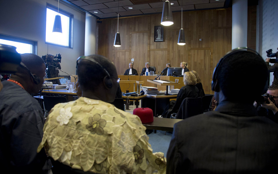 Judges, rear, and Nigerian plaintiffs, front, wait for the start of a court case of Nigerian farmers against Shell in The Hague, Netherlands, Thursday Oct. 11, 2012. Nigerian farmers are suing Shell in a Dutch court, asking judges to order the oil multinational to clean up environmental damage the farmers say is caused by leaking pipes. Thursday's case in The Hague Civil Court is a legal landmark in the Netherlands as it marks the first time a Dutch company has been sued for alleged environmental mismanagement caused by an overseas subsidiary. (AP Photo/Peter Dejong)