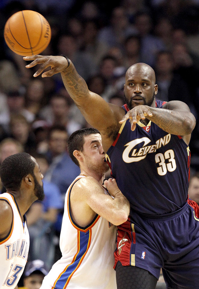 Photo - Cleveland's Shaquille O'Neal (33) passes the ball as Oklahoma City's Nick Collison (4) defends during the NBA game between the Oklahoma City Thunder and the Cleveland Cavaliers, Sunday, Dec. 13, 2009, at the Ford Center in Oklahoma City. Photo by Sarah Phipps, The Oklahoman