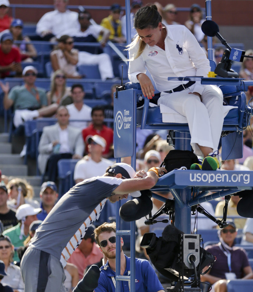 Photo - Tomas Berdych, of the Czech Republic, questions the chair umpires decision that a shot by Marin Cilic, of Croatia, bounced twice before hitting his racket during the quarterfinals of the 2014 U.S. Open tennis tournament, Thursday, Sept. 4, 2014, in New York. (AP Photo/Julio Cortez)