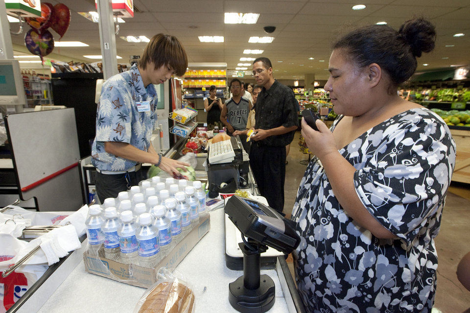 Photo - Times Supermarket employee Christopher Maeda, left, rings up water and food supplies for Charo Rodrigues Thursday, March 10, 2011 in Honolulu. The state of Hawaii is under a tsunami warning due to a large 8.9 earthquake off Japan. The earthquake is believed to have generated a tsumani wave. The Pacific Tsunami Center expects the wave to hit Hawaii at 2:59 a.m. Hawaiian Standard Time. (AP Photo/Eugene Tanner) ORG XMIT: HIET103