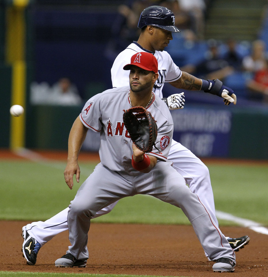 Photo -   Tampa Bay Rays' Desmond Jennings, background, gets back to first base ahead of the ball and tag by Los Angeles Angels first baseman Albert Pujols during the first inning of a baseball game, Thursday, April 26, 2012, in St. Petersburg, Fla. (AP Photo/Chris O'Meara)