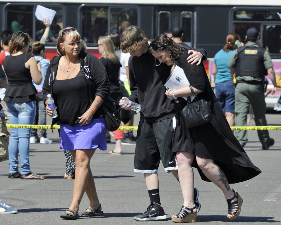 Photo - A family embraces after students arrived at the Fred Meyer grocery store parking lot in Wood Village, Ore., after a shooting at Reynolds High School Tuesday, June 10, 2014, in nearby Troutdale. A gunman killed a student at the high school east of Portland Tuesday and the shooter is also dead, police said. (AP Photo/Greg Wahl-Stephens)