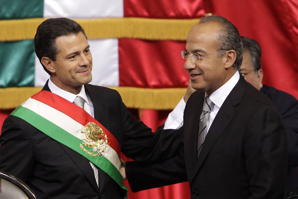 Photo - Mexico's incoming President, Enrique Pena Nieto, left, smiles as he stands with outgoing President Felipe Calderon during the inauguration ceremony at the National Congress in Mexico City, Saturday, Dec. 1, 2012.  Pena Nieto took the oath of office as Mexico's new president on Saturday, bringing the old ruling party back to power after a 12-year hiatus amid protests inside and outside the congressional chamber where he swore to protect the constitution and laws of the land. (AP Photo/Alexandre Meneghini)