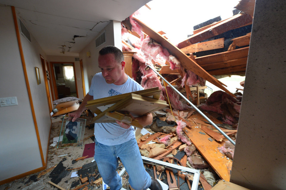 Photo - Josh Ramsey recovers items from a house of a family friend after a tornado left a path of devastation through the north end of Pekin, Ill., hitting right about noon Sunday, Nov. 17, 2013. Intense thunderstorms and tornadoes swept across the Midwest on Sunday, causing extensive damage in several central Illinois communities while sending people to their basements for shelter. (AP Photo/Journal Star, Fred Zwicky) MANDATORY CREDIT