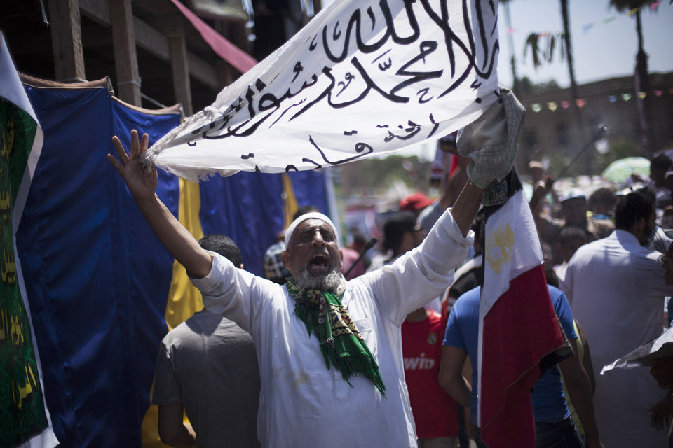 Photo - A supporter of Egypt's ousted President Mohammed Morsi chants slogans against the Egyptian Army during a protest near the University, in Giza, Egypt, Friday, July 26, 2013. Egyptian prosecutors accused ousted President Mohammed Morsi on Friday of conspiring with the Palestinian militant group Hamas and murder in his 2011 escape from prison that left 14 guards dead. The development fueled the likelihood of clashes as tens of thousands of supporters and opponents of the Islamist leader massed for rival rallies. (AP Photo/Manu Brabo)