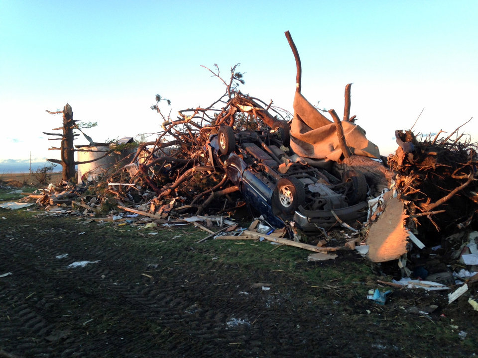 Photo - An overturned car rests on top of tree branches and other rubble near the destroyed home of Curt Zehr about a mile northeast of Washington, Ill., on Sunday, Nov. 17.  Intense thunderstorms spawning tornadoes swept across the Midwest on Sunday. (AP Photo/David Mercer)