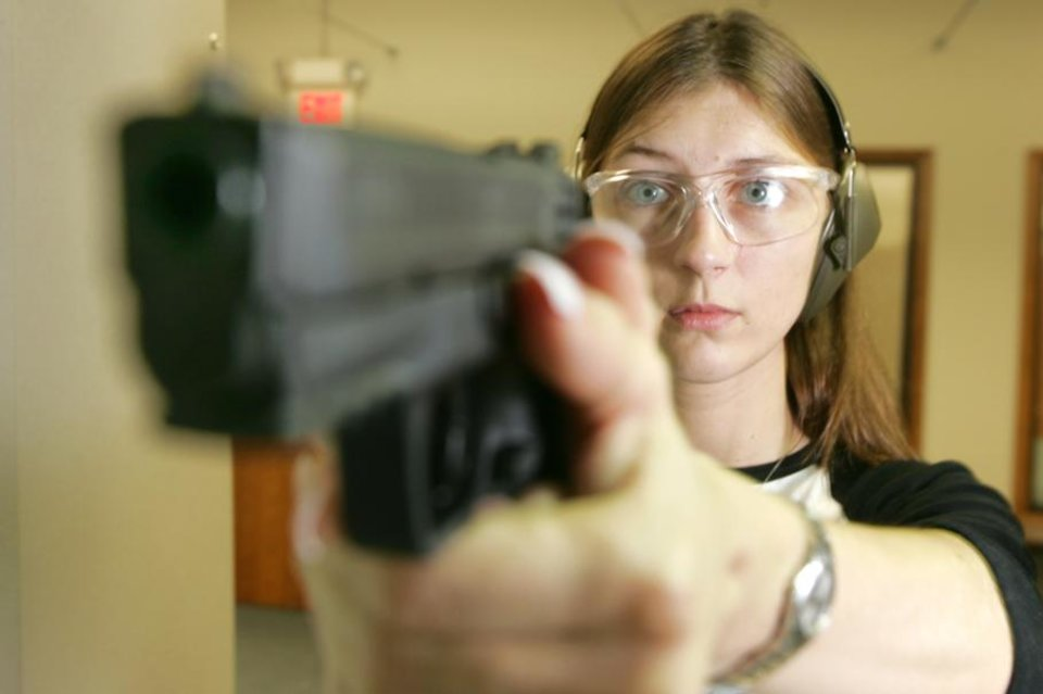 Photo - Cherie Potocki takes aim at her target at H&H Gun Range in Oklahoma City, Okla. June 26 , 2008. The Supreme Court ruled Thursday that Americans have a constitutional right to keep guns in their homes for self-defense, the justices' first major pronouncement on gun control in U.S. history.  BY STEVE GOOCH, THE  OKLAHOMAN.  ORG XMIT: KOD