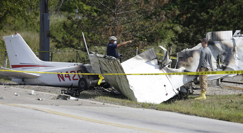 Photo - Investigators look over the wreckage of a plane crash as it rests on the side of a road Tuesday, Aug. 26, 2014, in Richmond Heights, Ohio. The Cessna 172R crashed and burst into flames just after takeoff from a regional airport outside of Cleveland on Monday, killing all four people on board, according to the Ohio State Highway Patrol.   School officials say the three passengers killed in he crash were members of the varsity wrestling team for Case Western Reserve University in Cleveland. (AP Photo/Tony Dejak)