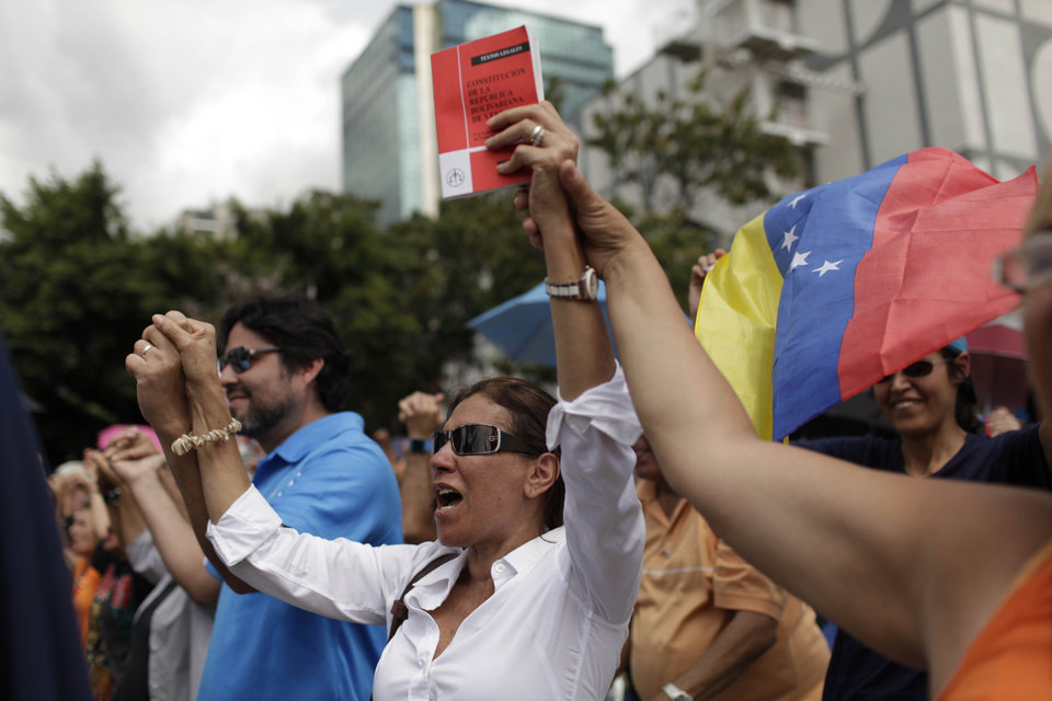 Photo - Opponents of Venezuela's President Hugo Chavez chant during an outdoor gathering in Caracas, Venezuela, Saturday, Jan. 12, 2013. Venezuelan opposition politicians say they're preparing to present a case before a regional human rights court to challenge a Supreme Court decision that permits the indefinite postponement of President Hugo Chavez's inauguration. (AP Photo/Ariana Cubillos)