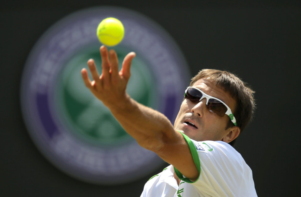 Photo - Tommy Robredo of Spain serves to Roger Federer of Switzerland during their men's singles match at the All England Lawn Tennis Championships in Wimbledon, London, Tuesday  July 1, 2014. (AP Photo/Pavel Golovkin)