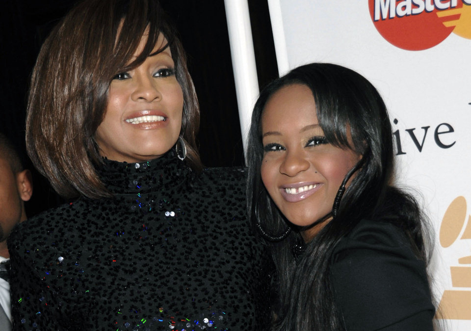 Photo - FILE - In this Feb. 12, 2011, file photo, singer Whitney Houston, left, and daughter Bobbi Kristina Brown arrive at an event in Beverly Hills, Calif.  The daughter of late singer and entertainer Whitney Houston was found Saturday, Jan. 31, 2015, unresponsive in a bathtub by her husband and a friend and taken to an Atlanta-area hospital. The incident remains under investigation.   (AP Photo/Dan Steinberg, File)