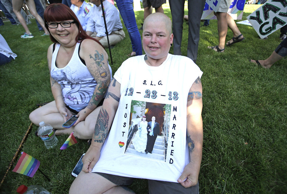 Photo - Dee Williams, right, displays her wedding photo on her t-shirt while her spouse Angie Braithwaite looks on as they gather with about 300 people in a downtown park to celebrate the gay marriage ruling Wednesday, June 25, 2014, in Salt Lake City. Williams and Braithwaite were married Dec. 23rd, 2013. A federal appeals court on Wednesday ruled for the first time that states must allow gay couples to marry, finding the Constitution protects same-sex relationships and putting a remarkable legal winning streak across the country one step closer to the U.S. Supreme Court. (AP Photo/Rick Bowmer)