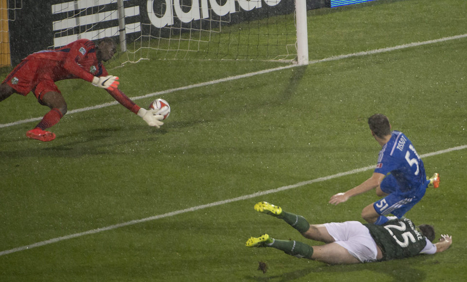 Photo - Montreal Impact's Maxim Tissot goes down as he scores Portland Timbers goalie Donovan Ricketts in front of Danny O'Rourke (25) during first half MLS action in Montreal on Sunday, July 27, 2014. (AP Photo/The Canadian Press, Peter McCabe)