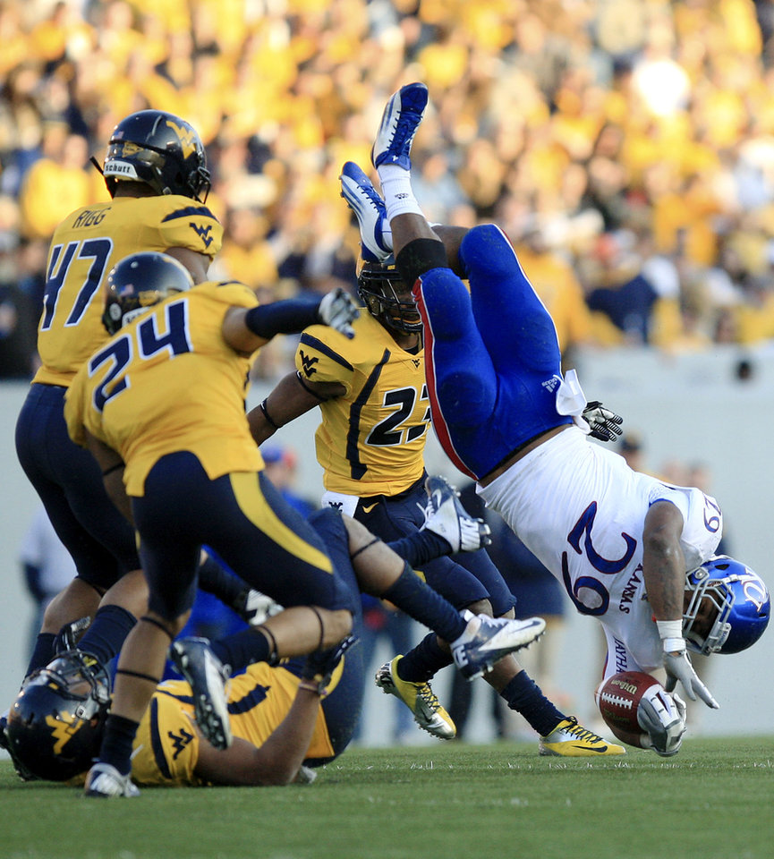 Photo - Kansas' James Sims (29) is tackled by West Virginia's Darwin Cook (25) during the second quarter of their NCAA college football game in Morgantown, W.Va., on Saturday, Dec. 1, 2012. (AP Photo/Christopher Jackson)