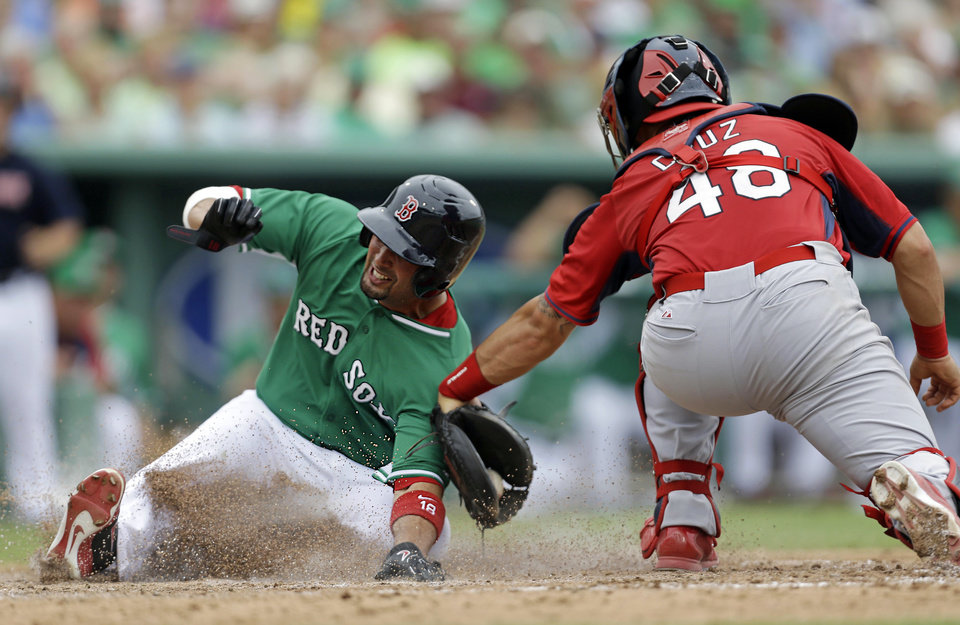 Photo - Boston Red Sox Shane Victorino, left, is tagged out at the plate by St. Louis Cardinals catcher Tony Cruz (48) on a fielders choice off the bat of David Ortiz in the fifth inning of an exhibition baseball game in Fort Myers, Fla., Monday, March 17, 2014. (AP Photo/Gerald Herbert)