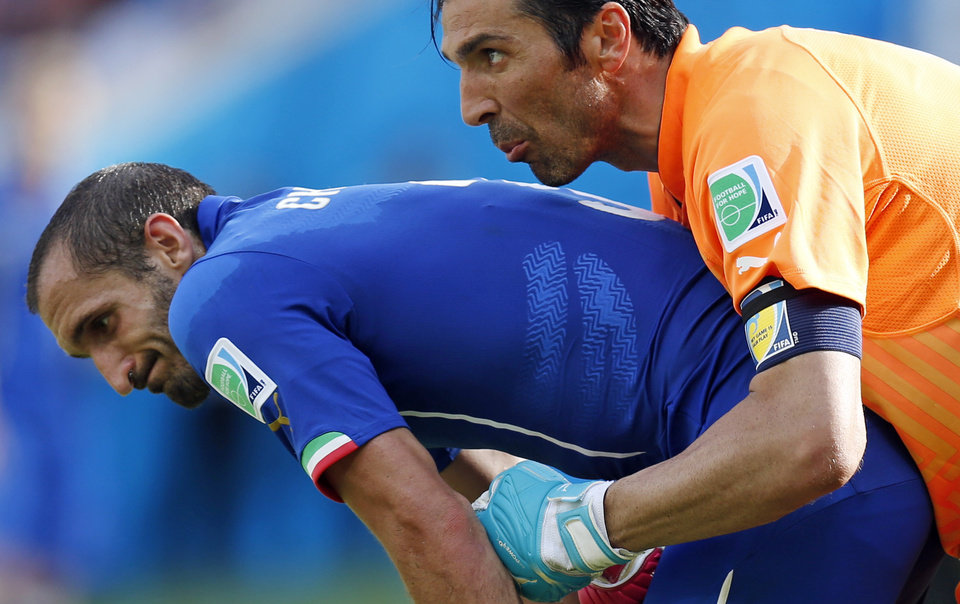 Photo - Italy's goalkeeper Gianluigi Buffon, right, holds on to Italy's Giorgio Chiellini during the group D World Cup soccer match between Italy and Costa Rica at the Arena Pernambuco in Recife, Brazil, Friday, June 20, 2014.  (AP Photo/Frank Augstein)