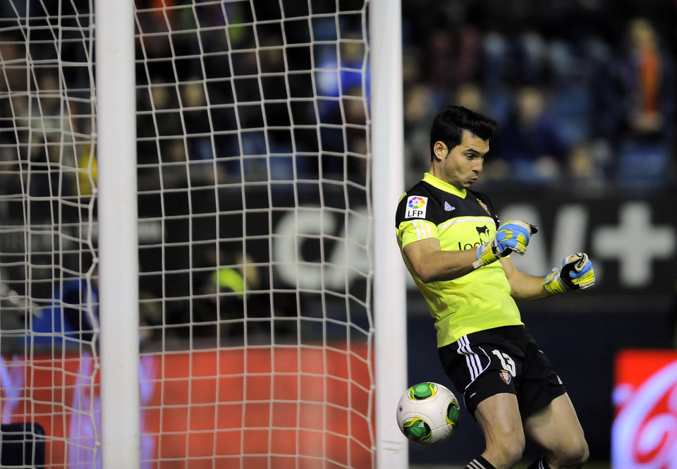 Photo - Real Madrid's Cristiano Ronaldo of Portugal scores past Osasuna's goalkeeper Andres Fernandez during their Spanish Copa del Rey round-16 second leg soccer match between Osasuna and Real Madrid , at El Sadar stadium, in Pamplona northern Spain on Wednesday, Jan. 15, 2014. (AP Photo/Alvaro Barrientos)