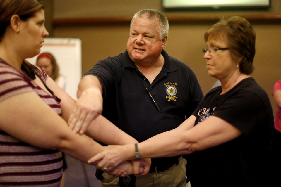 Photo - Norman police Sgt. Bob Moore shows a self-defense technique to Lori Buschbacher, left, and Monica Burks at a recent