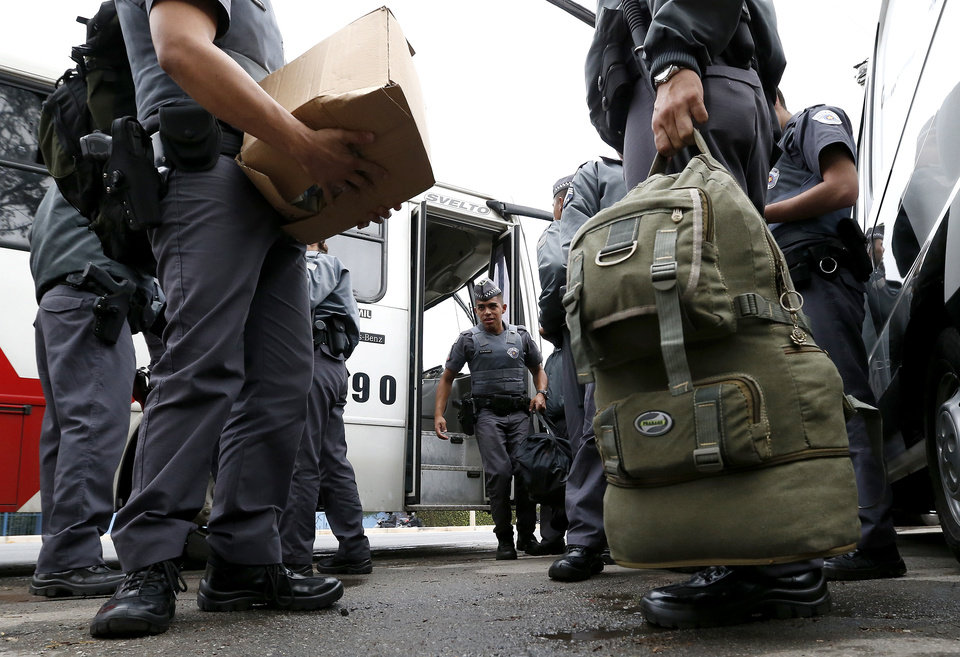 Photo - Police officers arrive at Sao Paulo FC training center before the United States arrived for a training session in Sao Paulo, Brazil, Tuesday, June 10, 2014. The U.S. will play in group G of the 2014 soccer World Cup. (AP Photo/Julio Cortez)
