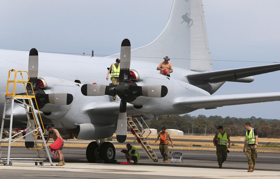Photo - In this photo taken March 25, 2014, ground crew work on a Royal Australian Air Force P-3 Orion at RAAF Base Pearce after the aircraft returns from the search for the missing Malaysia Airlines Flight 370 in Perth, Australia. The ground crew typically work on the tarmac through the night so the planes are ready to fly again by daylight, as the international effort to find some trace of the missing jetliner continues. (AP Photo/Rob Griffith)