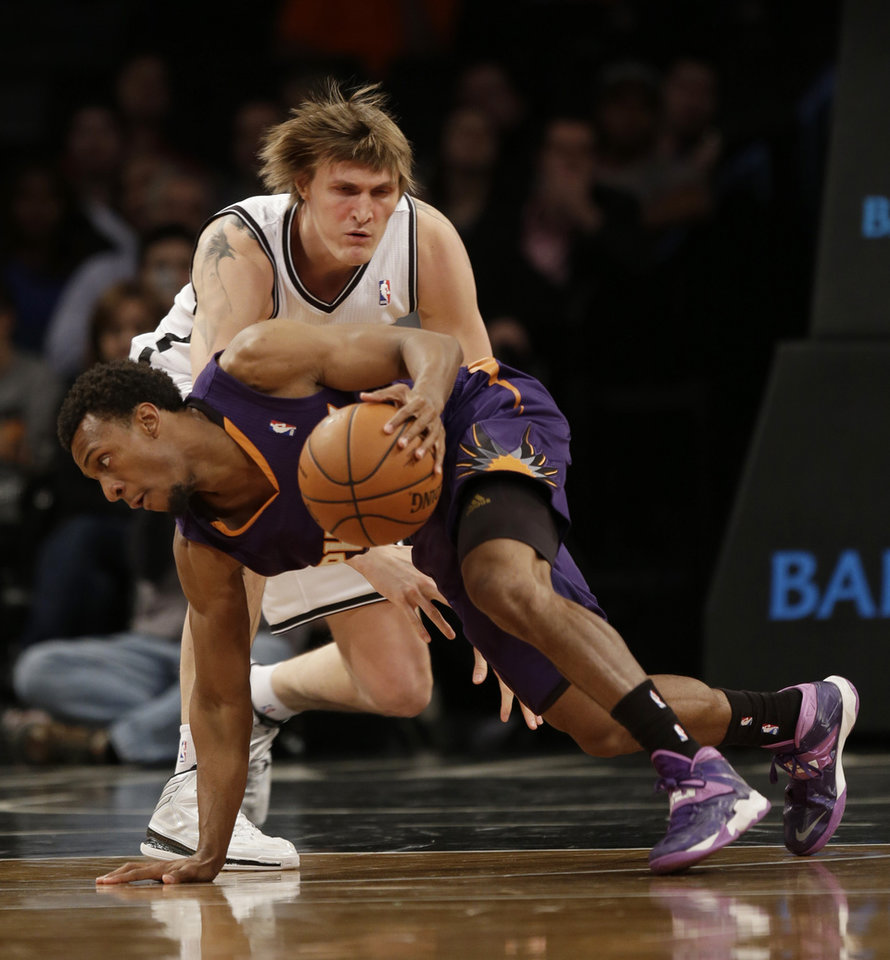 Photo - Phoenix Suns' Ish Smith, bottom, gets control of the ball while Brooklyn Nets's Andrei Kirilenko defends during the first half of the NBA basketball game at the Barclays Center Monday, March 17, 2014 in New York. (AP Photo/Seth Wenig)