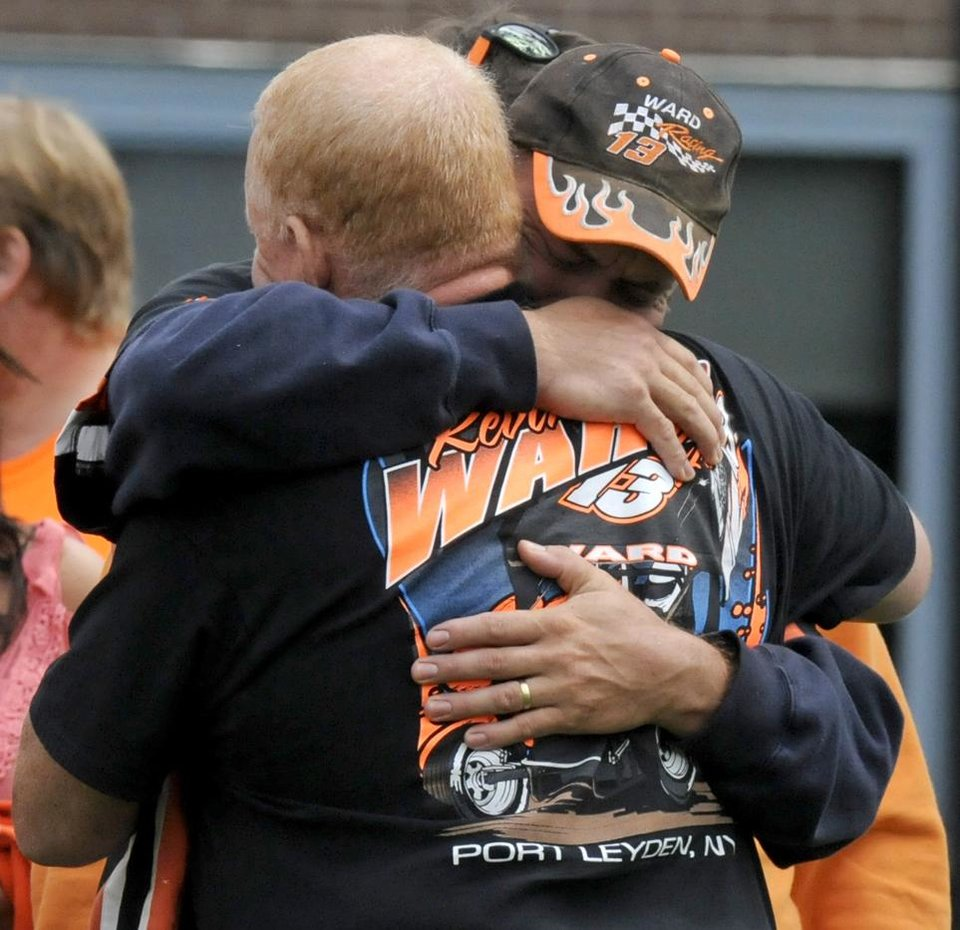 Photo - FILE - In this Aug. 14, 2014, file photo, people embrace outside the funeral service for Kevin Ward Jr. at South Lewis Central School in Turin, N.Y. Tony Stewart says the death of Ward will