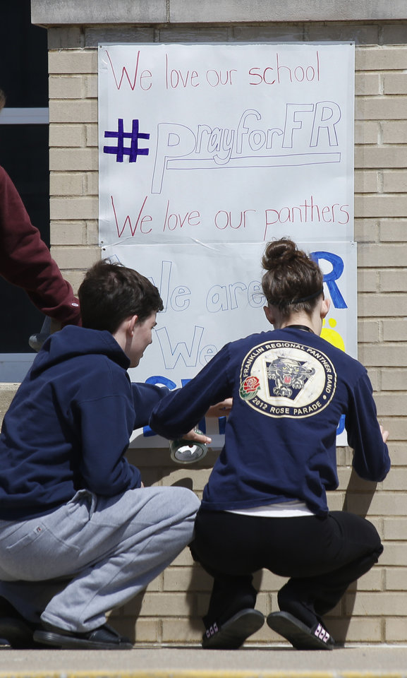 Photo - A group of students tapes up a sign supporting their school near the entrance to Franklin Regional High School Thursday, April 10, 2014 in Murrysville, Pa. A knife wielding student injured over 20 people in a stabbing attack the day before at the school. Authorities have charged Alex Hribal, 16, with four counts of attempted homicide and 21 counts of aggravated assault in the attack.  (AP Photo/Keith Srakocic)