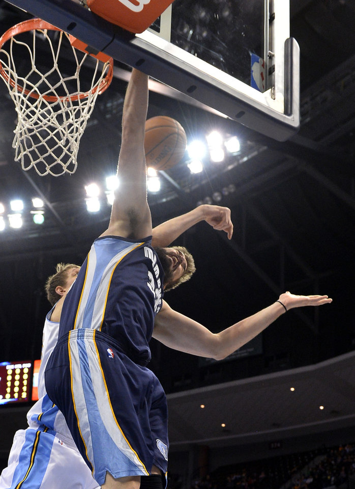 Photo - Denver Nuggets center Timofey Mozgov (25) from Russia fouls Memphis Grizzlies center Marc Gasol (33) from Spain during the second quarter of an NBA basketball game on Monday, March 31, 2014, in Denver. (AP Photo/Jack Dempsey)