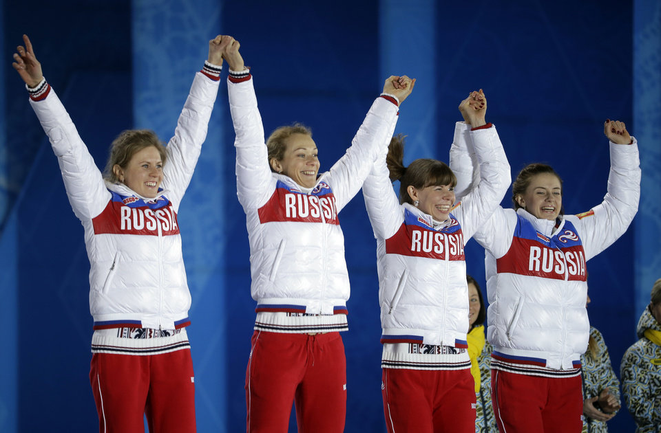 Photo - The team from Russia, who won the silver medal in the women's biathlon 4x6K relay, celebrate during their medals ceremony at the 2014 Winter Olympics, Saturday, Feb. 22, 2014, in Sochi, Russia. (AP Photo/Darron Cummings)