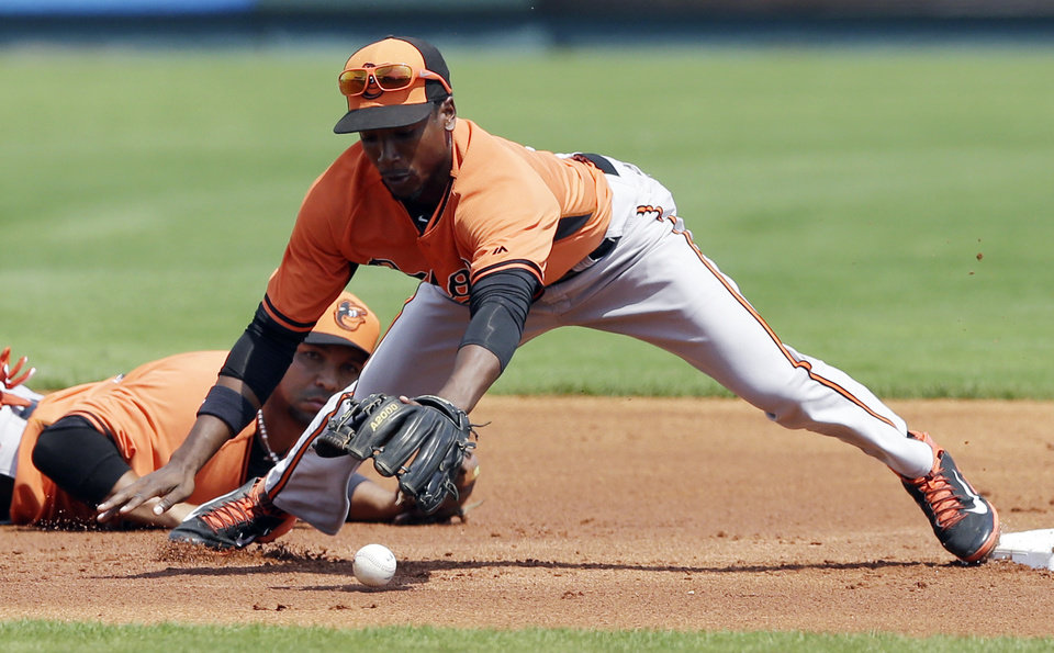 Photo - Baltimore Orioles second baseman Jemile Weeks reaches for the bobbled pitch from shortstop Alex Gonzalez, rear, during the first inning of a spring exhibition baseball game against the Pittsburgh Pirates in Bradenton, Fla., Monday, March 10, 2014. Pirates' Andrew McCutchen safely reached second. (AP Photo/Carlos Osorio)