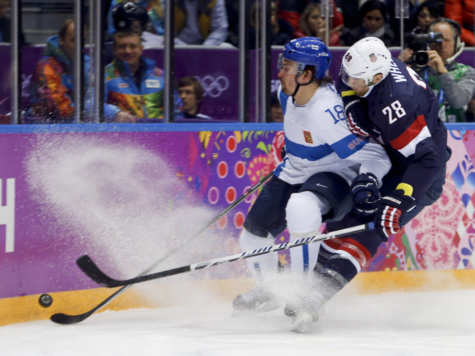 Photo - USA forward Blake Wheeler and Finland defenseman Sami Lepisto vie for the puck during the second period of the men's bronze medal ice hockey game at the 2014 Winter Olympics, Saturday, Feb. 22, 2014, in Sochi, Russia. (AP Photo/Petr David Josek)