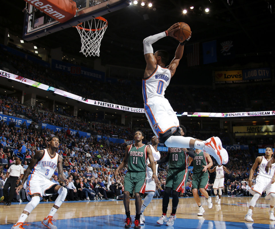 Photo - Oklahoma City's Russell Westbrook (0) goes up for a dunk during an NBA game between the Oklahoma City Thunder and the Milwaukee Bucks at Chesapeake Energy Arena in Oklahoma City, Tuesday, Dec. 9, 2014. Photo by Bryan Terry, The Oklahoman