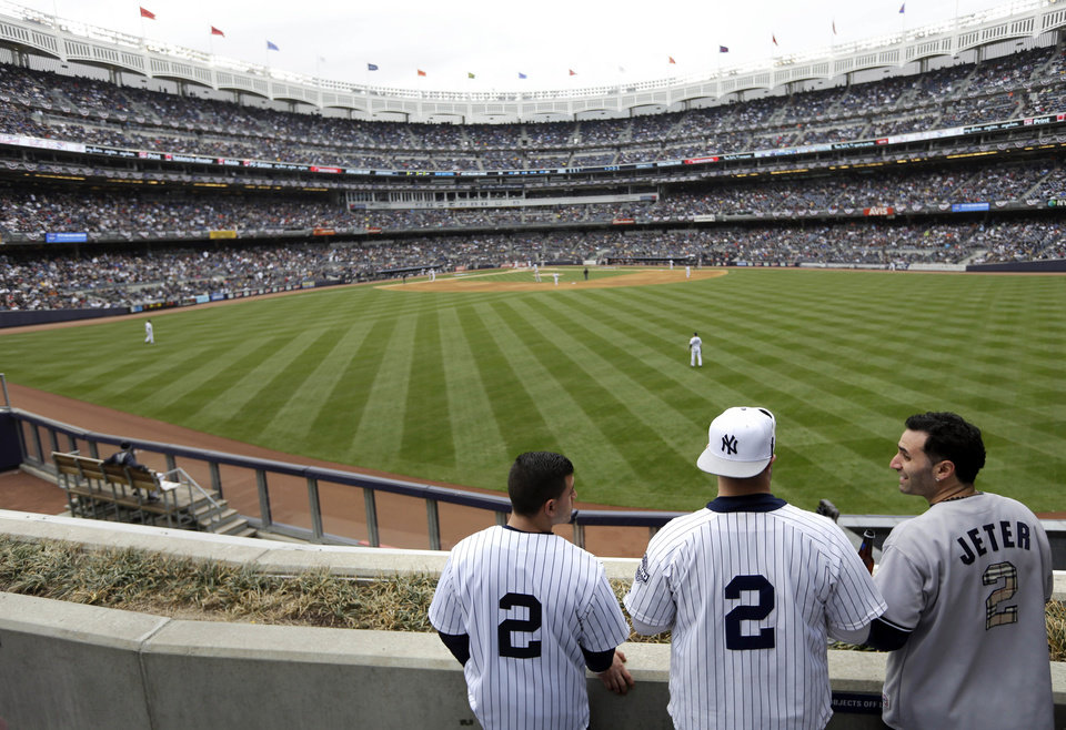 Photo - New York Yankees' fans wearing Derek Jeter's jersey watch the baseball game against the Baltimore Orioles at Yankee Stadium, Monday, April 7, 2014, in New York. (AP Photo/Seth Wenig)