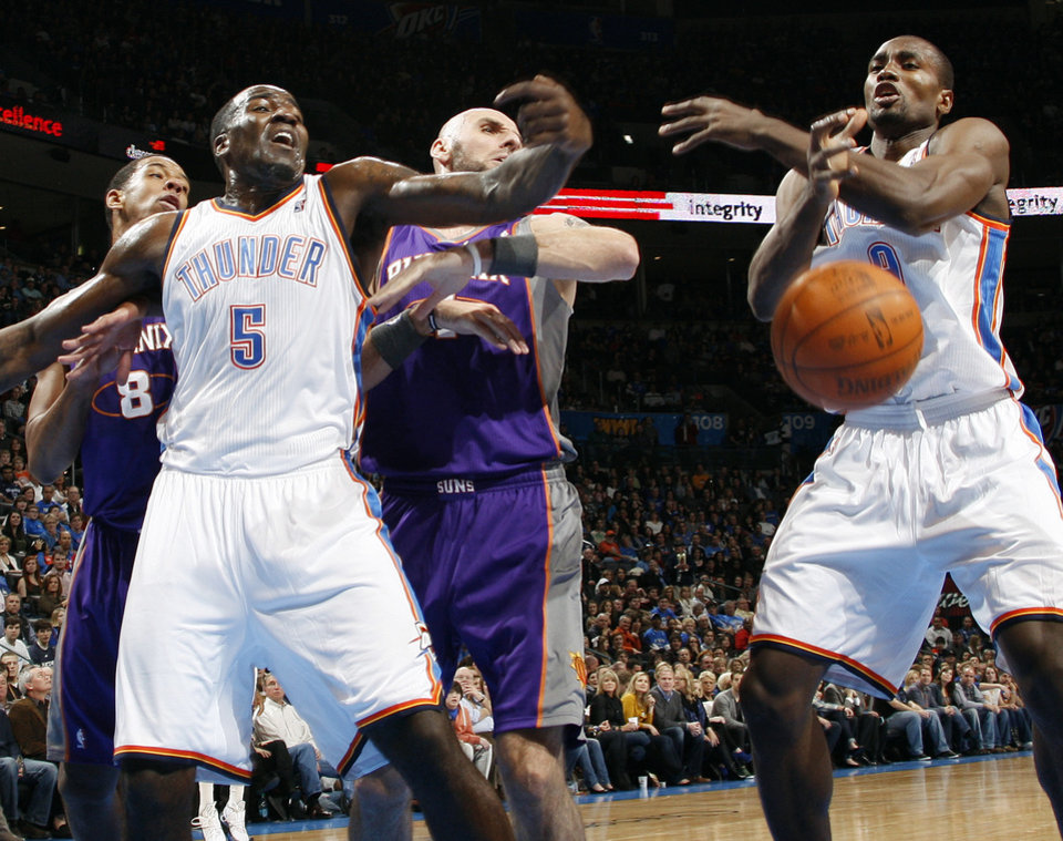 Photo - Oklahoma City's Kendrick Perkins (5) and Serge Ibaka (9) try to control the ball in front of Phoenix's Channing Frye (8) and Marcin Gortat (4) during the NBA basketball game between the Oklahoma City Thunder and Phoenix Suns at Chesapeake Energy Arena in Oklahoma City, Saturday, Dec. 31, 2011. Photo by Nate Billings, The Oklahoman