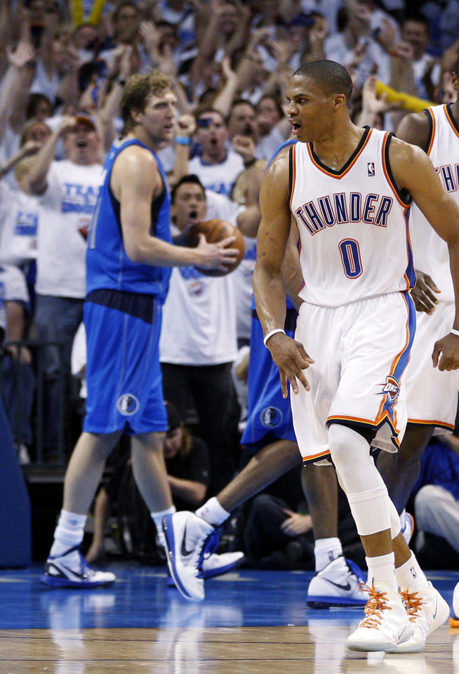 Photo -   Oklahoma City Thunder guard Russell Westbrook (0) reacts to a basket by teammate Derek Fisher, not in photo, in front of Dallas Mavericks forward Dirk Nowitzki, left, in the fourth quarter of Game 2 in the first round of the NBA basketball playoffs, in Oklahoma City, Monday, April 30, 2012. Oklahoma City won 102-99. (AP Photo/Sue Ogrocki)