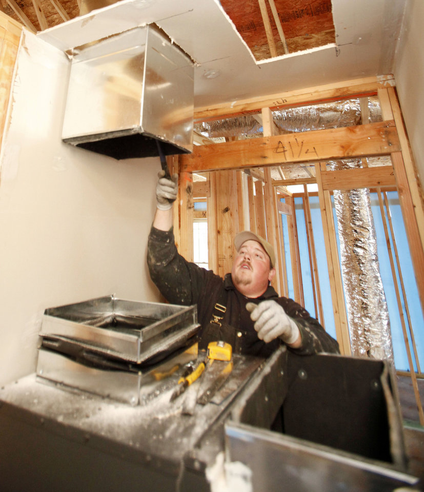 Eric Hensley works to install a geothermal heating-cooling system at 625 SE 26, in the Las Rosas neighborhood in Oklahoma City, OK, Monday, Feb. 13, 2012. By Paul Hellstern, The Oklahoman