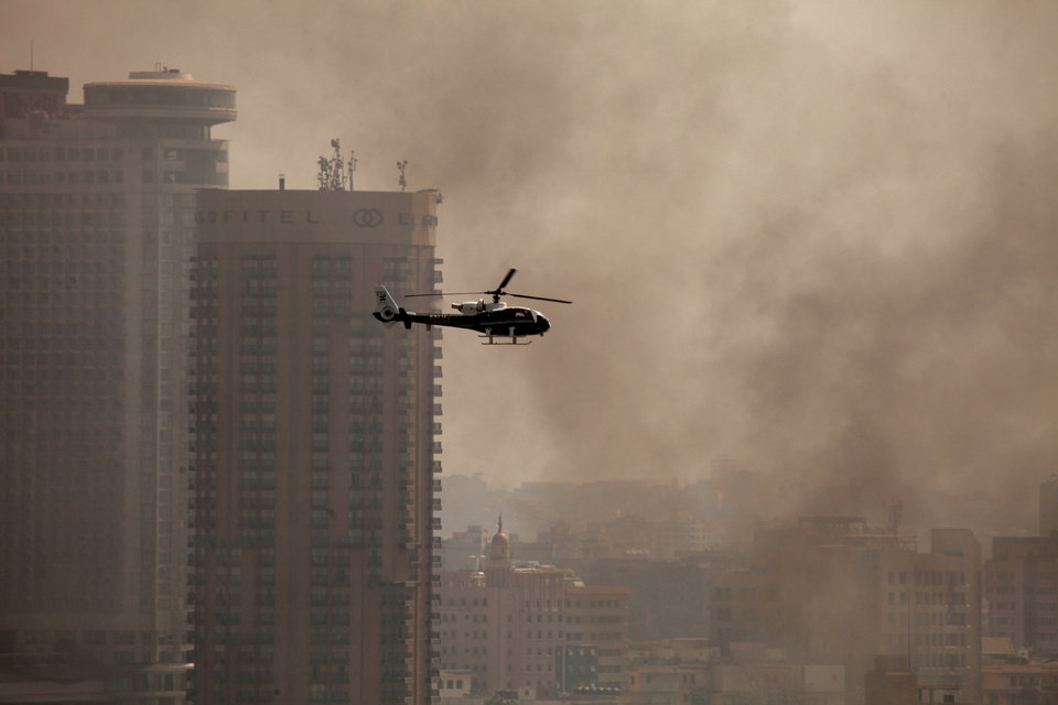 Photo - An Egyptian police helicopter flies through smoke from fires set by protesters at a police officers club and the Egyptian Soccer Federation  following a court verdict in Cairo, Egypt, Saturday, March 9, 2013. Fans of Cairo's Al-Ahly club have stormed Egypt's soccer federation headquarters and a nearby police club and set them ablaze after a court acquitted seven of nine police official on trial for their alleged part in deadly stadium melee. (AP Photo/Maya Alleruzzo)