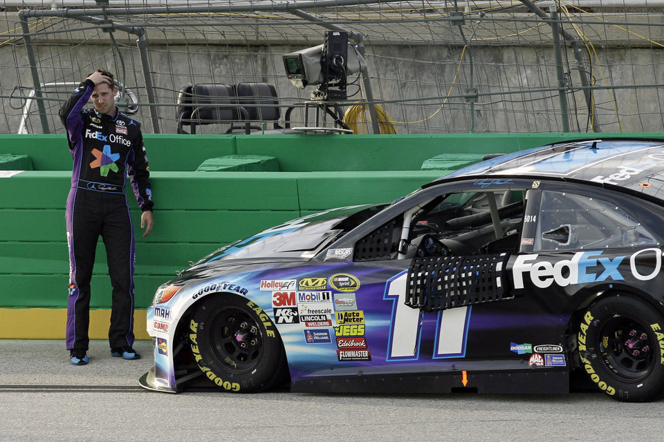 Photo - Denny Hamlin reacts after seeing the damage to the right side of his car following a collision with the outside wall during the NASCAR Sprint Cup series auto race Saturday, June  28, 2014, at Kentucky Speedway in Sparta, Ky. The accident put Hamlin out of the race. (AP Photo/Garry Jones)
