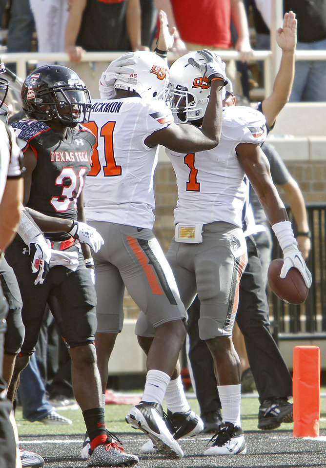 Photo - Oklahoma State Cowboys wide receiver Justin Blackmon (81) and Joseph Randle (1) celebrate a touchdown next to Texas Tech Red Raiders cornerback Eugene Neboh (31) during the college football game between the Oklahoma State University Cowboys (OSU) and Texas Tech University Red Raiders (TTU) at Jones AT&T Stadium on Saturday, Nov. 12, 2011. in Lubbock, Texas.  Photo by Chris Landsberger, The Oklahoman  ORG XMIT: KOD