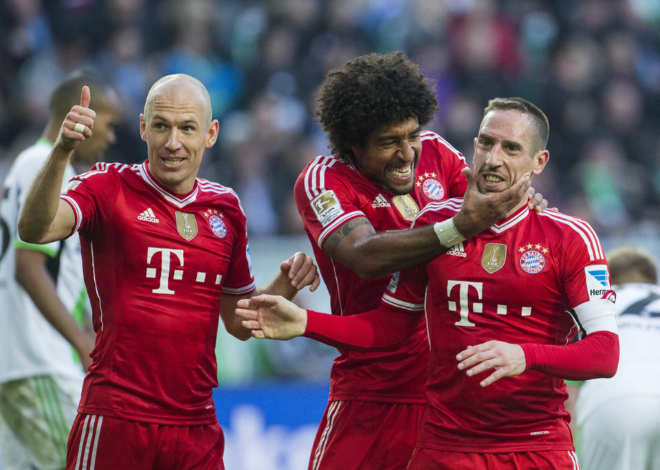 Photo - From left, Bayern's Arjen Robben of the Netherlands, Bayern's Dante of Brazil and Bayern's Franck Ribery of France celebrate after Robben scored his side's 4th goal during the German Bundesliga soccer match between VfL Wolfsburg and Bayern Munich in Wolfsburg, Germany, Saturday, March 8, 2014. (AP Photo/Gero Breloer)